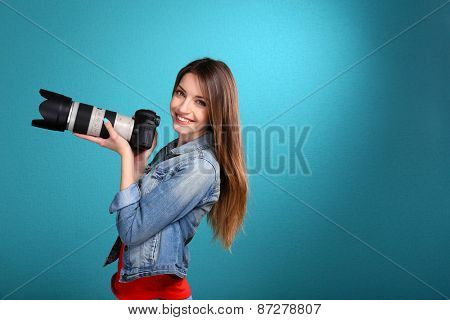 Young female photographer taking photos on blue background