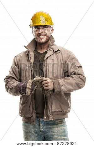 Young Dirty Worker Man With Hard Hat Helmet  .holding A Work Gloves And Smiling