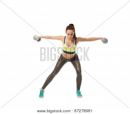 Harmonous girl training with dumbbells at camera