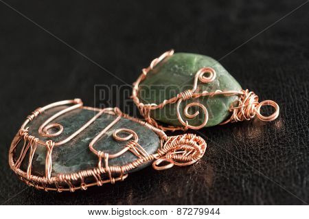 Two Pendents Of Handwork Against A Dark Background