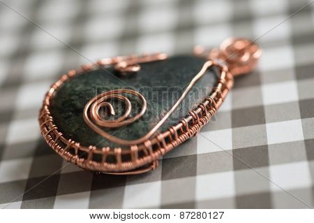 Wire Wrapped Pendant On A Checkered Background Close Up