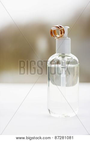 Plastic Bottle With A Lubricant And Two Wedding Rings