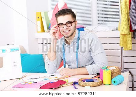 Young man fashion designer in atelier