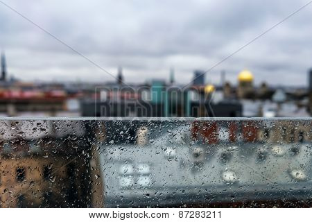 Roofs And Spiers Of The City Behind A Glass Partition In The Rain