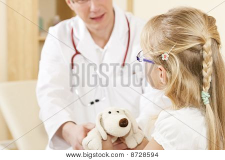 Child giving a soft toy to doctor