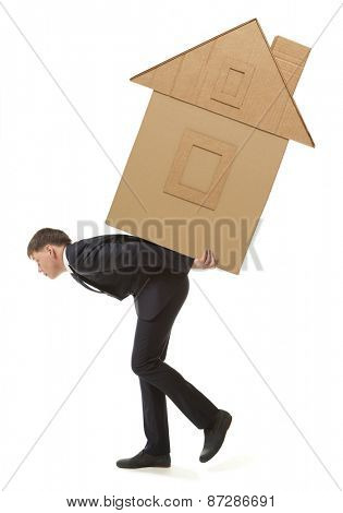 Young businessman lifting huge model of paper house