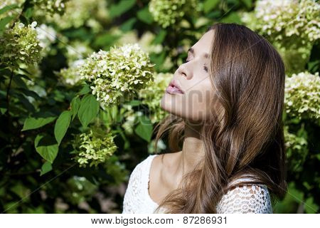 Portrait of beautiful brunette in spring blossom