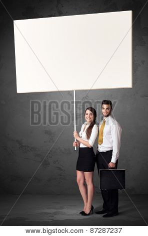 Young business couple holding a blank whiteboard