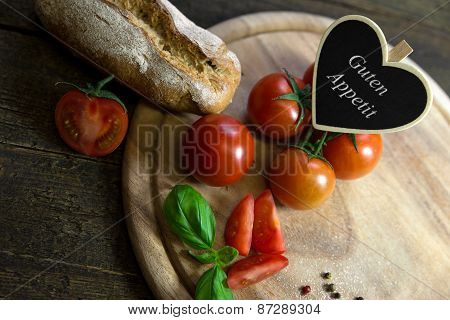 Tomatoes, Basil And Bread On A Wooden Table, Heart With Text Guten Appetit