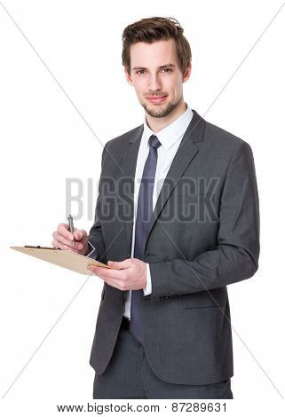 Businessman takes notes on clipboard