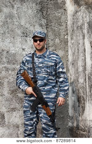 Caucasian Man With Black Sunglasses In Urban Warfare Holding Grifle