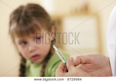 Pediatrician doctor applying syringe to child