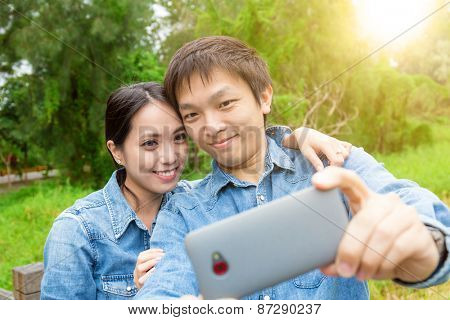Young asian couple take selfie in park