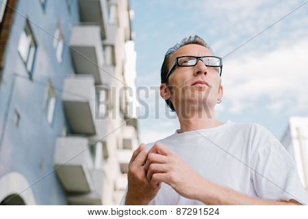 mid-aged man in front of city building.