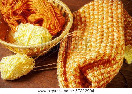 Woolen Yarn And Knitting On Wooden Background.