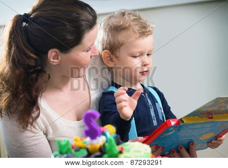 Mother and son looking at children's game