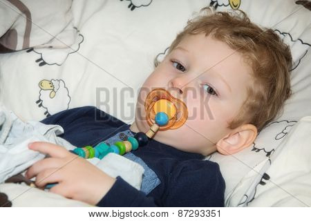 2-year-old boy with pacifier before falling asleep in bed