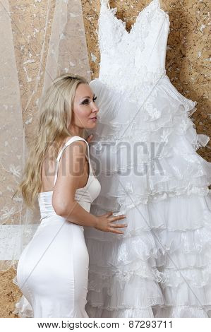 The beautiful woman the bride near wedding dress dreams about wedding