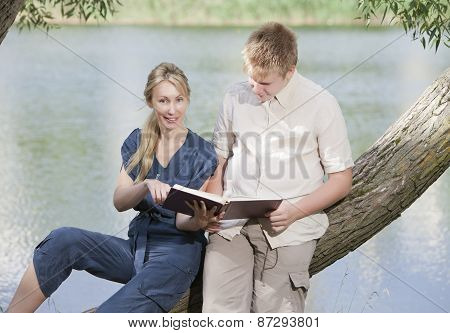 Young guy and the girl with textbooks on the bank of lake