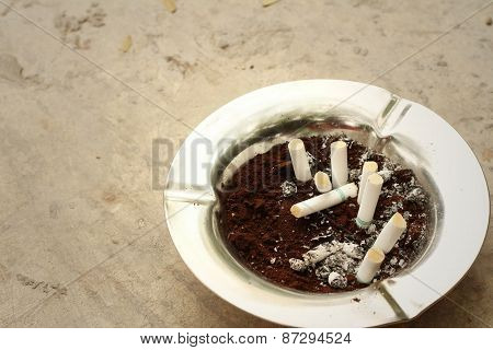 Cigarette With Ashtray On The Floor At The Park