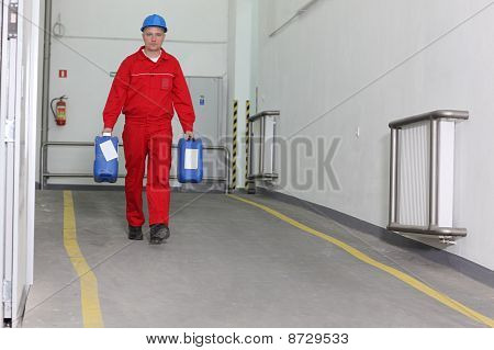 Factory worker carrying bottles of chemicals
