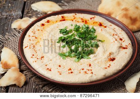 Bowl of hummus, traditional mediterranean smooth salad with oil, paprika and parsley