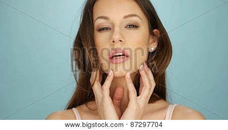 Gorgeous laughing playful young woman with a beaming smile looking to the right of the frame, head and shoulders over blue
