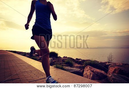 young woman runner  running at seaside. woman fitness silhouette sunrise jogging workout wellness co