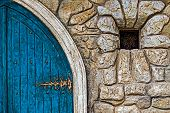 stock photo of wall-stone  - Stone wall texture background with ancient blue door to the castle and small window - JPG