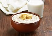 stock photo of porridge  - Porridge oats with banana slices and glass of milk on wooden table - JPG
