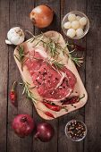 picture of ribeye steak  - Raw ribeye beef steak on wooden board with rosemary and peppercorn - JPG