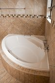 stock photo of tile  - A white corner bath in a tiled bathroom the tiles are of different shades of brown - JPG