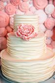stock photo of eatables  - white wedding cake with signle eatable pink rose - JPG