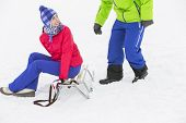 picture of sled  - Happy young woman sitting on sled while looking at man in snow - JPG