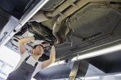 foto of car repair shop  - Low angle view of male automobile mechanic repairing car in repair shop - JPG