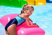 picture of inflatable slide  - Child on blue water slide at aquapark - JPG
