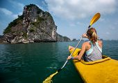 image of kayak  - Woman exploring calm tropical bay with limestone mountains by kayak - JPG