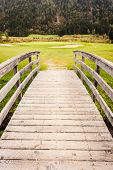 image of old bridge  - an old wooden bridge on an idyllic meadow or a beautiful golf course