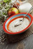 stock photo of porridge  - Porridge and red apples on a wooden table - JPG