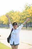 image of hands-free  - young beautiful woman wearing white shirts straw hat and sun glasses rising hand victory shape and toothy smiling use for modern and people lifestyle feeling free - JPG