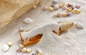 picture of suntanning  - bottle of suntan oil covered by sand with shells and cap - JPG
