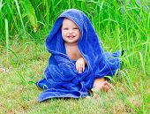 foto of naked children  - Little child sitting on the grass with blue towel - JPG