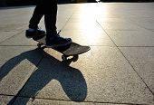 stock photo of skateboarding  - woman skateboarder legs skateboarding at sunrise city - JPG