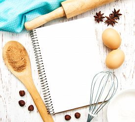 stock photo of pastry chef  - blank recipe book with baking ingredients on a old wooden background - JPG