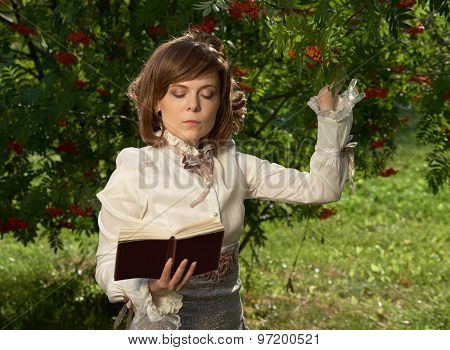 Girl Touches Rowan Berries And Reads Book