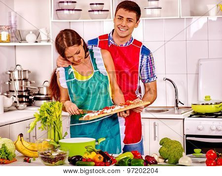 Couple cooking dinner at kitchen.