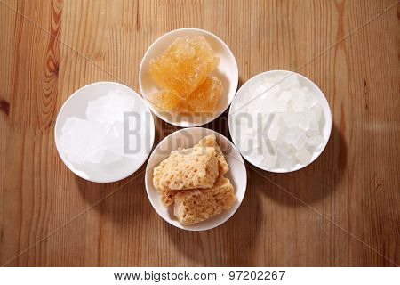 Four type of sugar  in white bowls, white wood table background