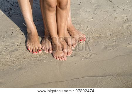 Feet Of Child And Mom In The Sea Sand
