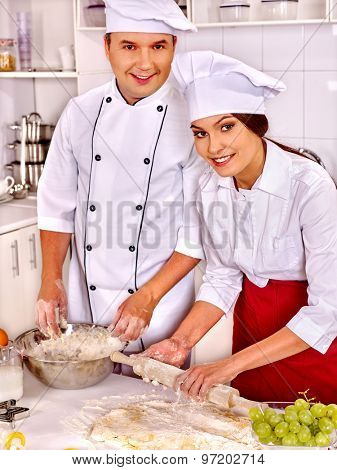 Happy woman and man in chef hat cooking dough .Grapes in foreground