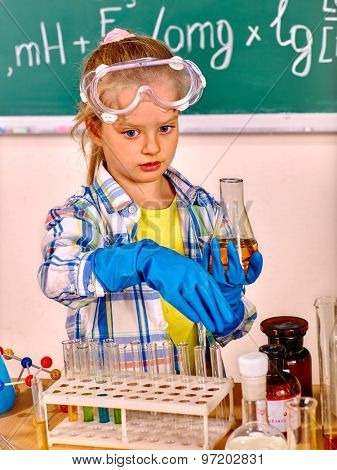Child in glove holding flask in chemistry class.